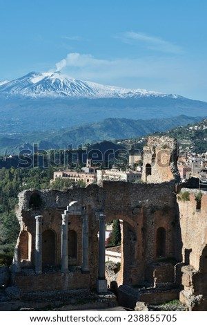 Ruins of the ancient greek theater of Taormina, Sicily the Etna with its smoke tail in the background above the morning sun lit Giardini-Naxos bay of the Ionian see. - stock photo