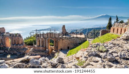Ruins of the ancient greek theater of Taormina, Sicily with the smoking Etna and the morning sun lit Giardini-Naxos bay of the Ionian see in the background. Taormina, Sicily, Italy - stock photo