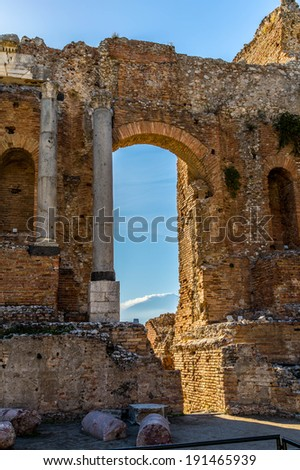 Ruins of the ancient greek theater with Corinthian columns backlit by the sun at noon with the Etna in the background in Taormina, Sicily - stock photo