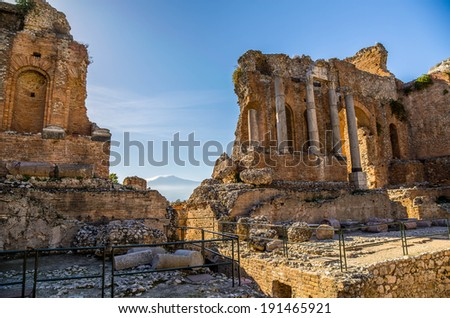 Ruins of the ancient greek theater with Corinthian columns backlit by the sun at noons itch the Etna in the background  in Taormina, Sicily - stock photo