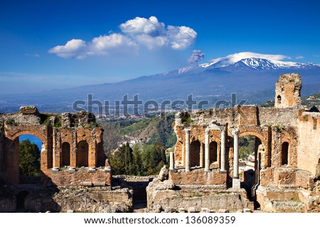 Ruins of the Greek Roman Theater with Etna erupting, Taormina, Sicily, Italy - stock photo