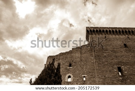 Ruins of the medieval castle and cypress tree before a storm. (Chateauneuf du Pape, Provence, France) Nature and architecture background. Aged photo. Sepia.