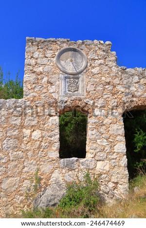 Ruins of Venetian building decorated with solar clock, Dalmatian coast, Croatia - stock photo