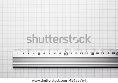 Ruler aligned to a scaled paper. For showing actual size of a object - stock photo