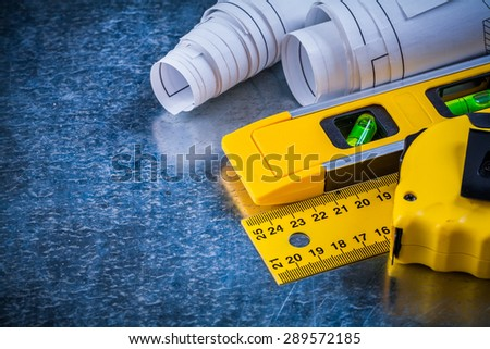 Ruler measuring tape construction level and blueprints on metallic scratched background building and architecture concept. - stock photo