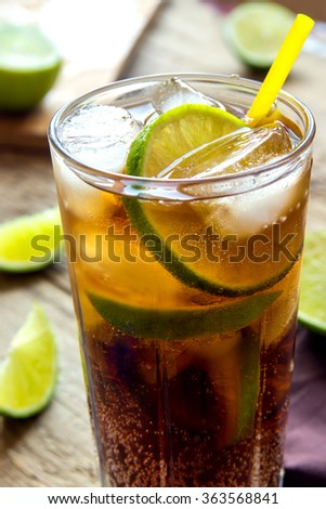 Rum and cola Cuba Libre drink with lime and ice on rustic wooden table