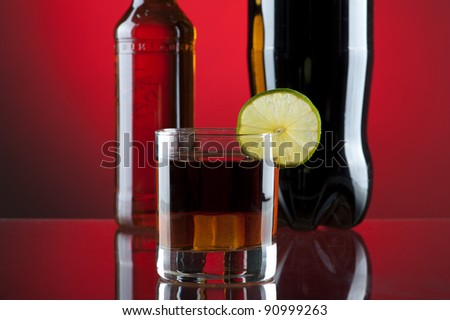 Rum-cola cocktail on red background - stock photo