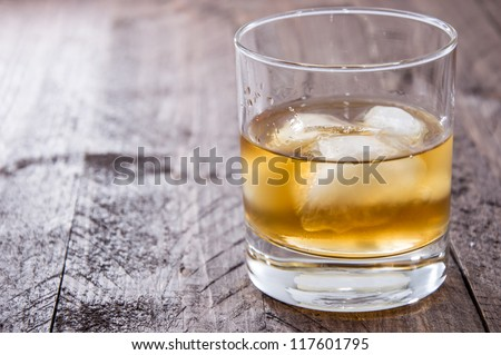 Rum on the rocks on wooden background