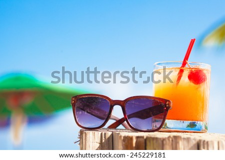Rum punch cocktail and sunglasses at tropical beach. - stock photo
