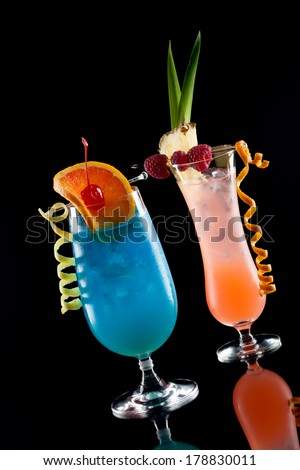 Rum Runner and Blue Lagoon cocktaisl over black background on reflection surface, garnished with pineapple flag, fresh raspberry, maraschino cherry, and orange twist. Most popular cocktails series.  - stock photo