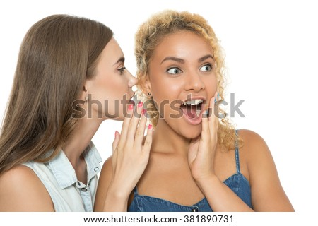 Rumor has it all. Portrait of two close friends, one girl whispering a secret in the ear of her friend looking very amazed and astonished, isolated on white background - stock photo