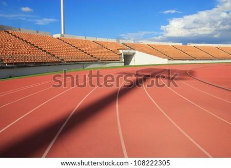 Run race track in sport stadium ,Spot light shadow - stock photo