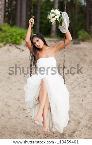 Runaway bride sitting on a swing - stock photo