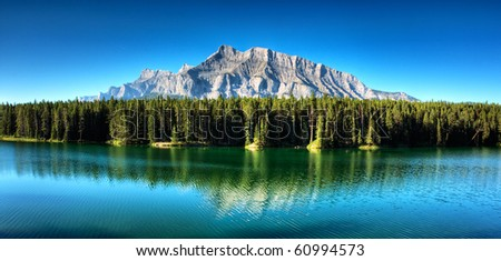 Rundle Mountain reflection in Johnson Lake, in Banff National Park. - stock photo