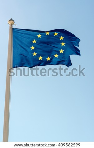 Rundown blue flag of the European Union against great blue sky. The flag is torn off at the side, maybe a symbol for problems around the EU and its members? - stock photo