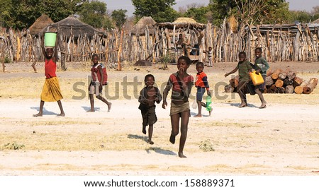 RUNDU, NAMIBIA - SEPTEMBER 7: Unidentified children fetching water on september 7, 2010 in a small village near Rundu, Namibia. - stock photo