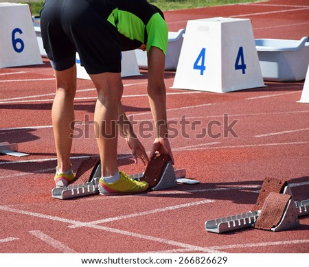 Runner at the starting line of the running track - stock photo