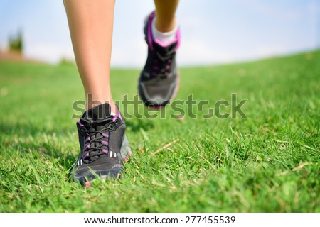 Runner athlete feet running on grass. Fitness woman jog workout and wellness concept. Close up of female running shoes and legs. - stock photo