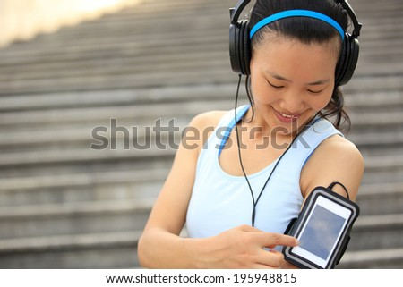 Runner athlete listening to music in headphones from smart phone mp3 player smart phone armband.woman fitness jogging workout wellness concept.  - stock photo