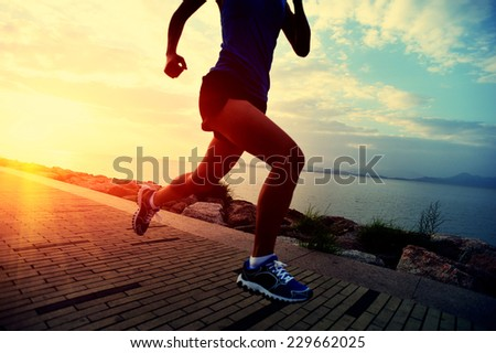 Runner athlete running at seaside. woman fitness sunrise jogging workout wellness concept.  - stock photo