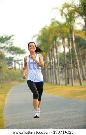 Runner athlete running at tropical park road. woman fitness jogging workout wellness concept.  - stock photo
