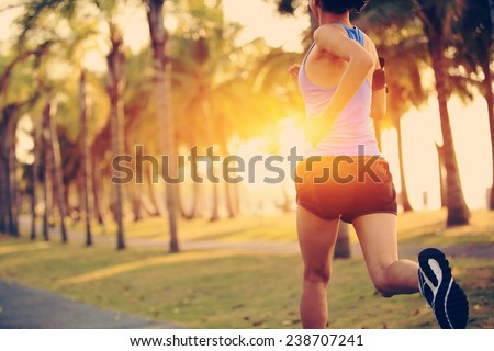 Runner athlete running at tropical park. woman fitness jogging workout wellness concept.  - stock photo