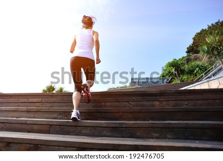 Runner athlete running at wooden stairs. woman fitness jogging workout wellness concept.  - stock photo