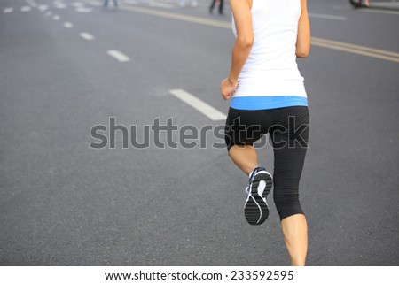 Runner athlete running on city road. woman fitness jogging workout wellness concept.  - stock photo