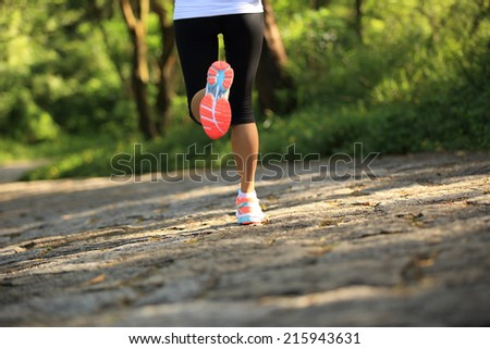 Runner athlete running on forest trail. woman fitness jogging workout wellness concept.  - stock photo