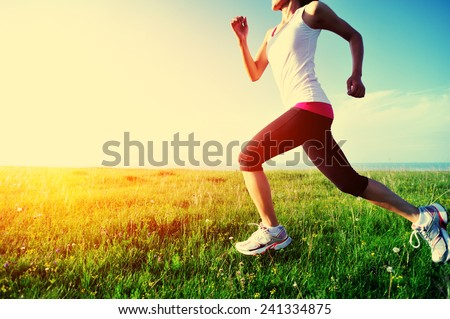 Runner athlete running on grass seaside. woman fitness sunset jogging workout wellness concept.  - stock photo