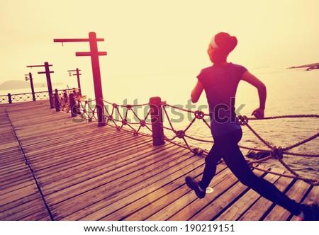 Runner athlete running on seaside wooden pier. woman fitness jogging workout wellness concept.  - stock photo