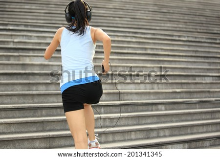 Runner athlete running on stairs. listening to music in headphones from smart phone mp3 player woman fitness jogging workout wellness concept.
