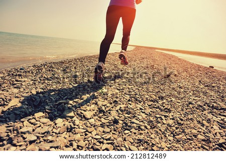 Runner athlete running on stone beach. woman fitness jogging workout wellness concept.
