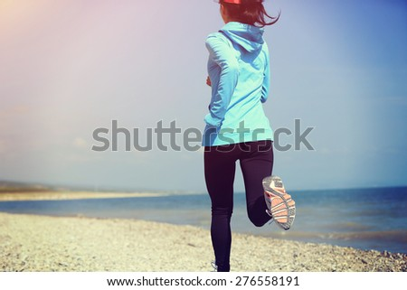 Runner athlete running on stone beach . woman fitness jogging workout wellness concept.  - stock photo