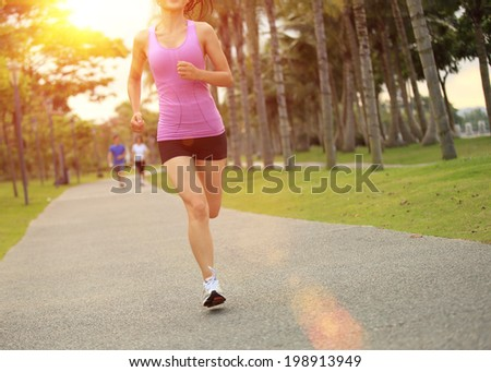 Runner athlete running on tropical park trail. woman fitness jogging workout wellness concept.