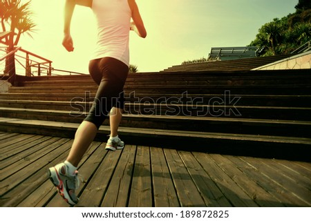 Runner athlete running on wooden stairs. woman fitness jogging  workout wellness concept.  - stock photo