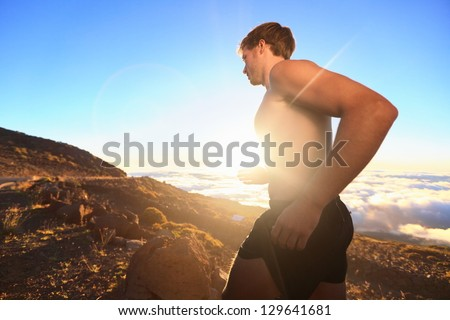 Runner athlete running. Sport man jogging outdoor in sunshine at sunset in scenic nature. Fit muscular male fitness guy training trail running for marathon run. Sporty fit athletic man working out. - stock photo