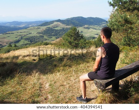 Runner athlete sitting on bench and resting in mountains, looking into the distance. Summer, Pieniny, Poland. - stock photo