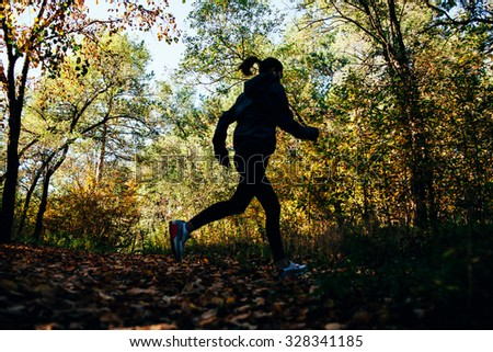 runner caucasian woman  jogging in autumn park, silhouette out of focus - stock photo
