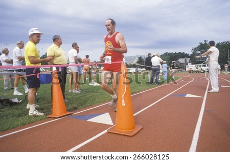 Runner crosses the finishing line at the Senior Olympics, St. Louis, MO