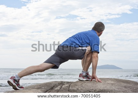 Runner doing stretching exercise on a rock at the sea - stock photo