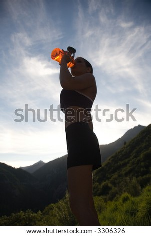 Runner drinking water in a silhouette - stock photo
