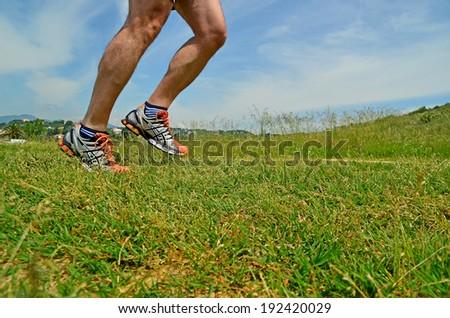 runner feet - close up - grass - jogging - stock photo