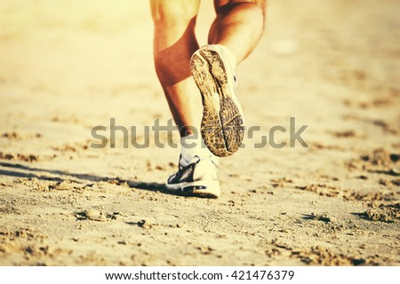 Runner feet running on beach closeup on shoe - stock photo