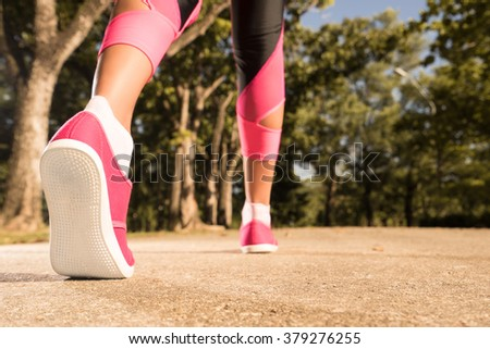 Runner feet running on road closeup on shoe. woman fitness concept.