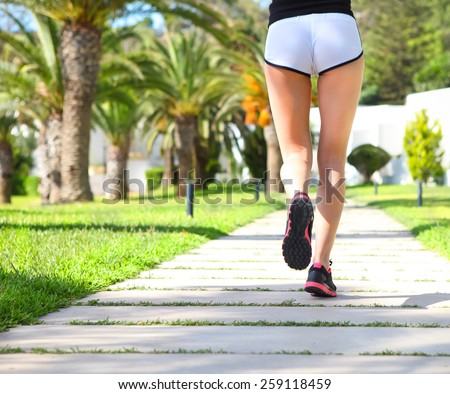 Runner feet running on road in the park. cCloseup on shoes. Woman fitness sunrise jog workout welness concept - stock photo