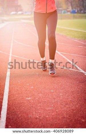 Runner feet running on stadium track closeup - woman running concept. Sunny Day