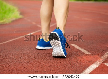 runner feet running on track and closeup of shoe. workout wellness concept