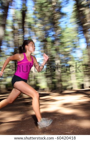 Runner, Female running fast in forest. Motion blurred image of beautiful Asian / Caucasian woman athlete sprinting outdoors in tank top - copy space. - stock photo