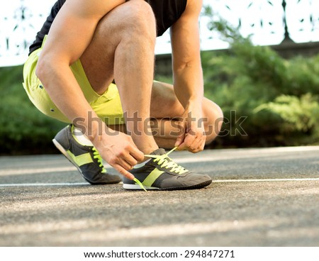 Runner getting ready for jogging tying running shoes laces. Man preparing before run putting on trainers. - stock photo